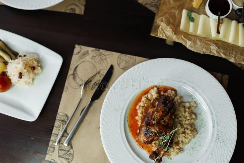Gamba fritta appetitosa dell'anatra in salsa di funghi con i supporti del porridge dell'orzo su una tavola di legno in un caffè V fotografia stock