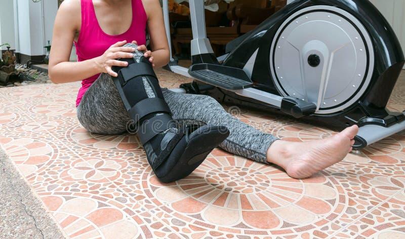 gamba rotta, abiti sportivi della donna di lesione e cavigliera d'uso, l fotografie stock