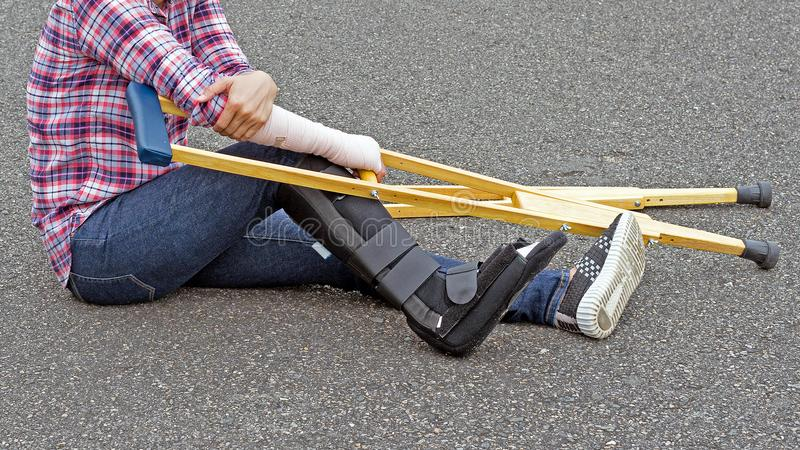gamba rotta, camicia della donna di lesione e jeans d'uso con lo splin del braccio immagini stock libere da diritti