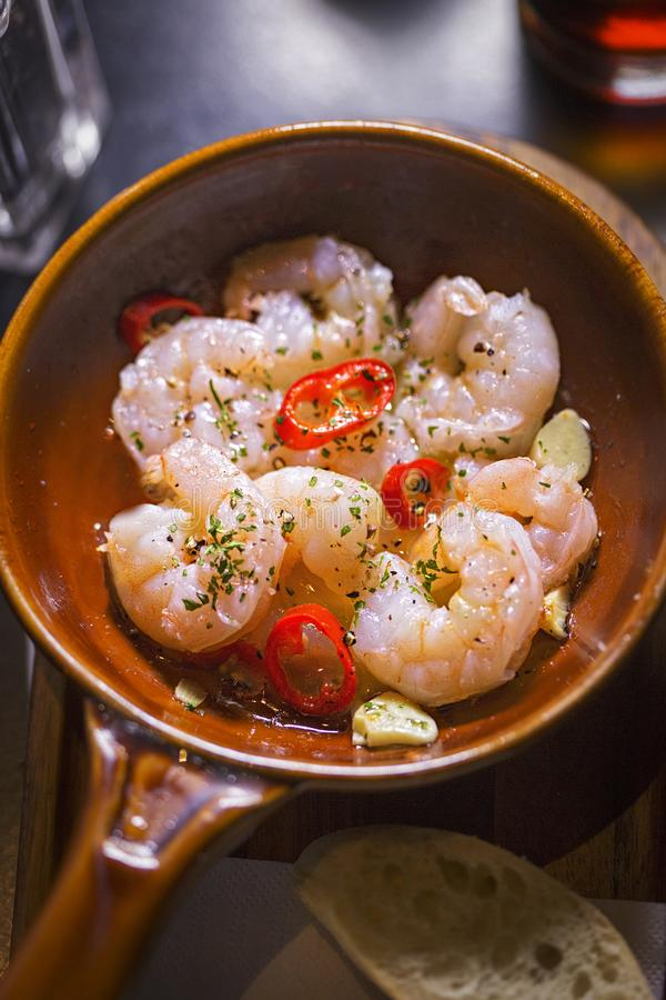 Gambas al Ajillo. Prawns cooked in Virgin Oil with Garlic and Chilli royalty free stock image