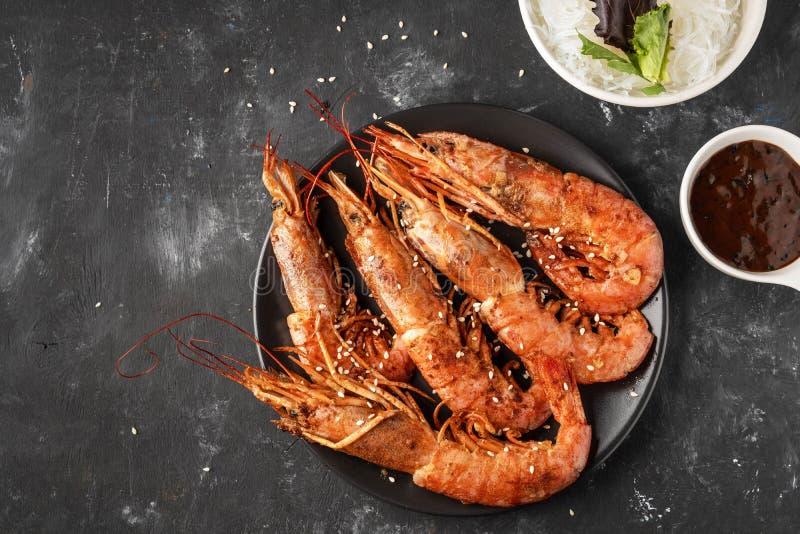 Gambas asadas a la parrilla fritas con los tallarines de arroz, la salsa y la lechuga, fondo oscuro fotografía de archivo libre de regalías