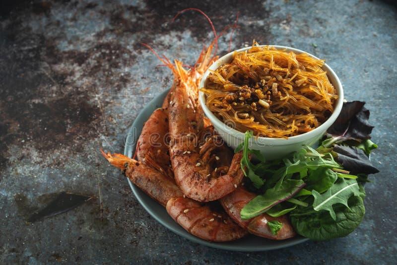 Gambas asadas a la parrilla fritas con los tallarines de arroz, la salsa y la lechuga, fondo oscuro foto de archivo