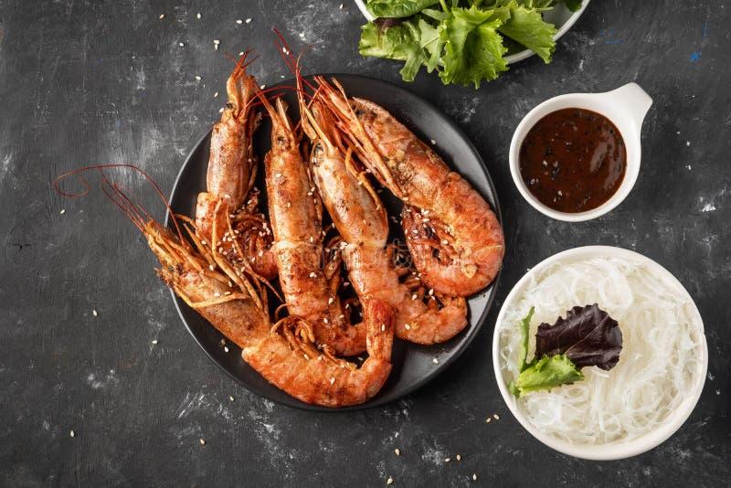 Gambas asadas a la parrilla fritas con los tallarines de arroz, la salsa y la lechuga, fondo oscuro imagen de archivo libre de regalías