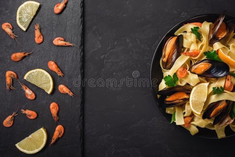 Gambas crudas frescas o camarones rojos hervidos con las especias y el limón en piedra de la pizarra en fondo de piedra oscuro Ma imagen de archivo libre de regalías