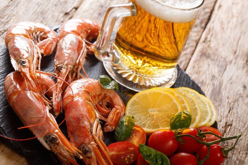 Gambas deliciosas del rey con la cerveza ligera, el limón y el primer de los tomates en un tablero de la pizarra horizontal imagenes de archivo