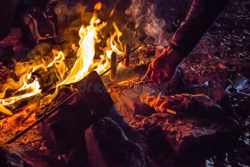 Gambas y salchichas de la asación en Live Coals foto de archivo libre de regalías