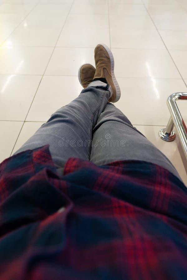 Gambe attraversate di un uomo in pantaloni grigi e scarpe marroni L'uomo nella sala di attesa fotografia stock