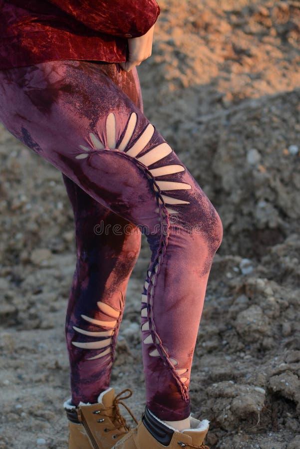 Gambe in belle e calzamaglia tagliate uniche, modo di festival, ora dorata, sera calda immagine stock