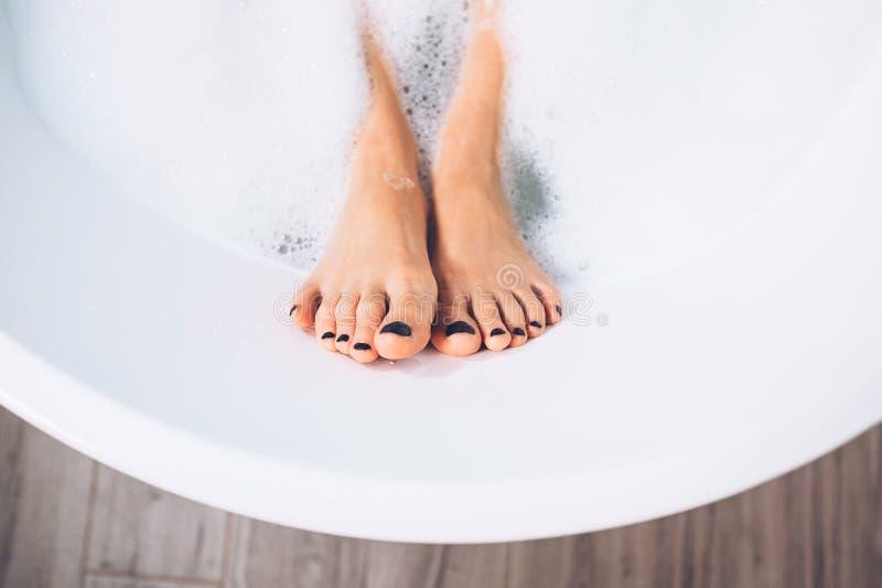 Gambe ben curato del ` s della donna nella fine della schiuma del bagno sull'immagine fotografia stock libera da diritti