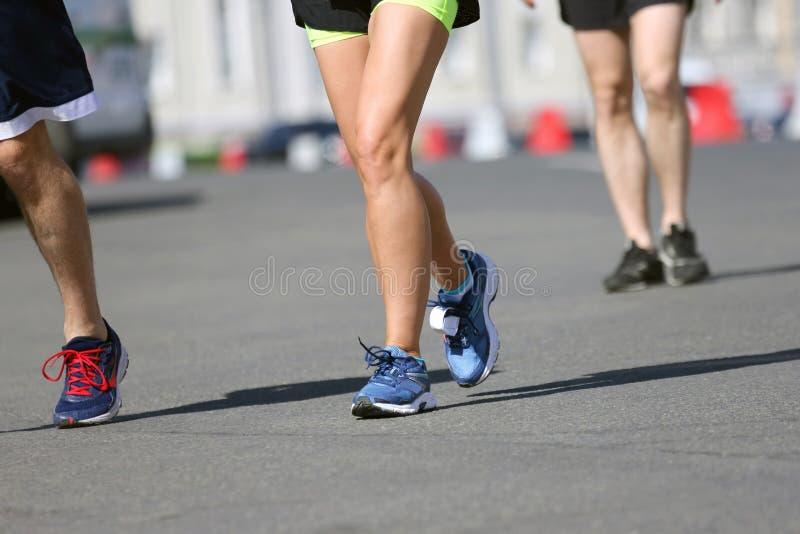 Gambe che eseguono gli atleti sul corso immagine stock