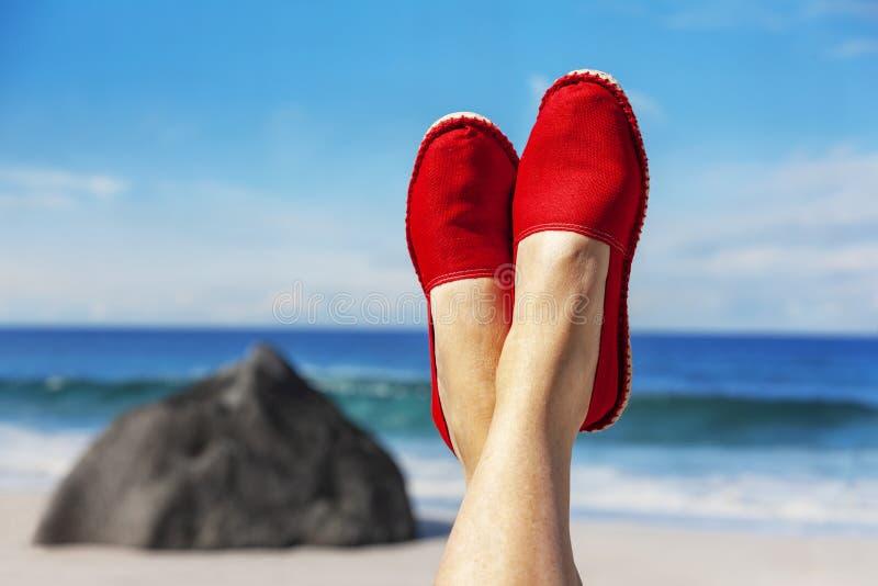 Gambe con le scarpe rosse del panno davanti alla spiaggia immagine stock