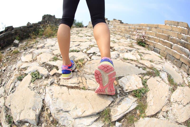Gambe del corridore della donna che corrono sulla grande muraglia fotografia stock libera da diritti