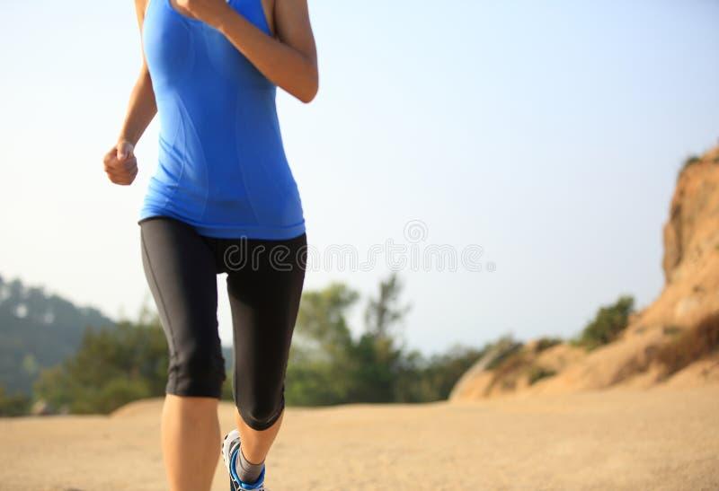 gambe del corridore della donna che corrono sulla traccia di montagna fotografia stock libera da diritti