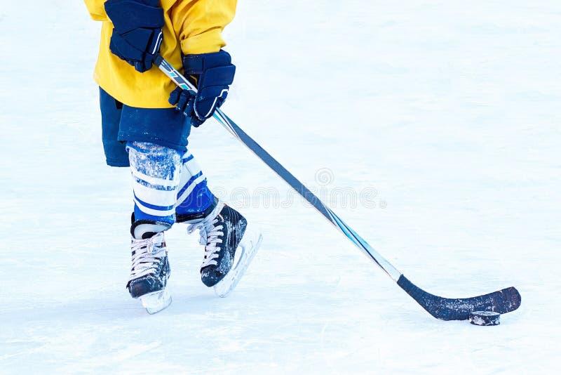 Gambe del giocatore di hockey, del bastone e del primo piano della rondella immagini stock libere da diritti