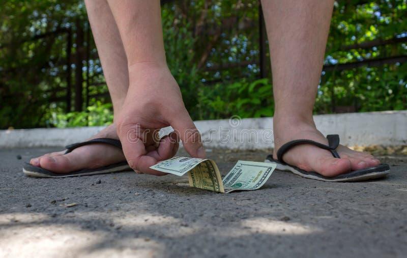 Gambe del primo piano di un adolescente che prende i dollari americani di una banconota immagini stock libere da diritti