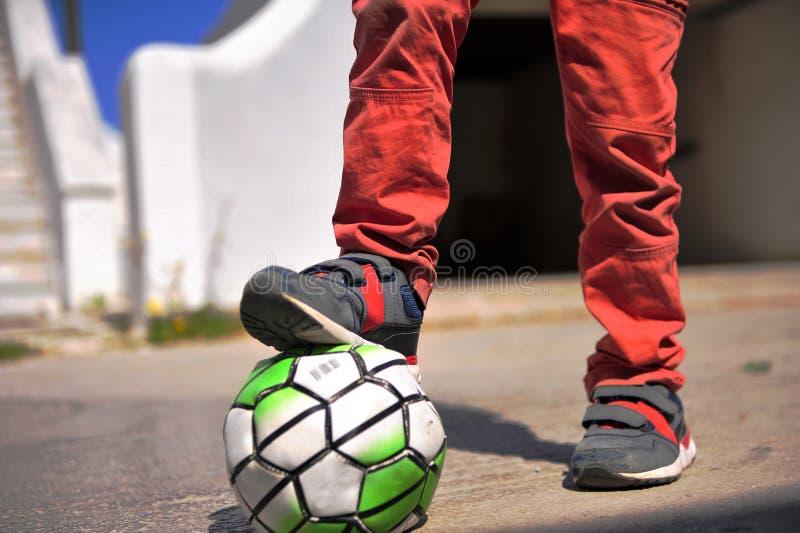 Gambe del ` s del bambino con calcio immagini stock libere da diritti