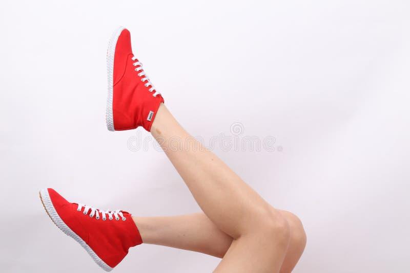 Gambe del ` s della donna con Tomy Takkie Trainers rosso immagine stock libera da diritti
