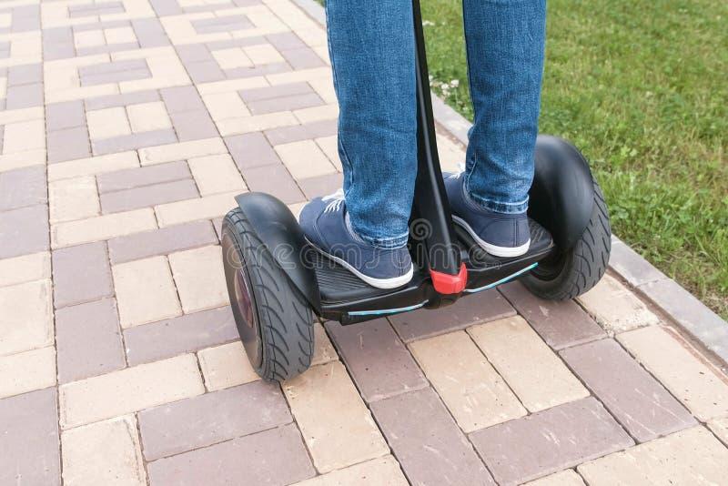 Gambe del ` s della persona in scarpe da tennis che rotolano sul motorino della girobussola sulla pavimentazione della strada Vis immagine stock