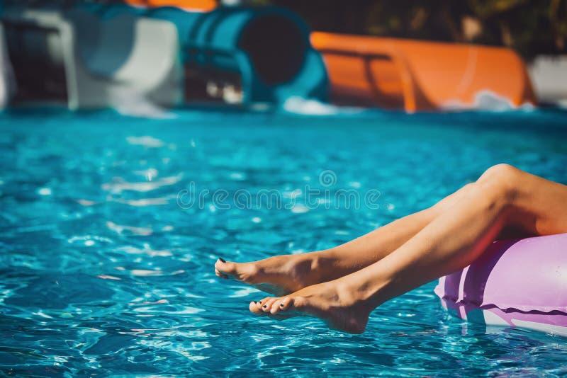 Gambe del ` s della ragazza nella piscina fotografia stock libera da diritti
