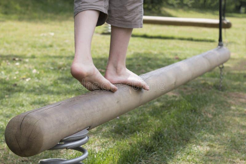 Gambe del ` s del ragazzo su un fascio di equilibrio immagine stock