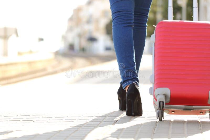 Gambe del viaggiatore che camminano con i bagagli in una stazione ferroviaria fotografie stock