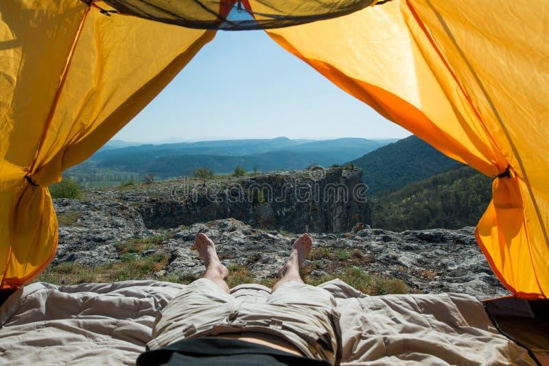 Gambe del viaggiatore in una tenda di campeggio all'aperto fotografia stock libera da diritti