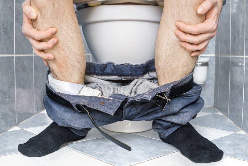 Gambe dell'uomo con diarrea che sta sedendosi sulla toilette immagini stock libere da diritti