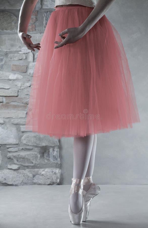 Gambe della ballerina con le scarpe del pointe nella quinta posizione immagini stock