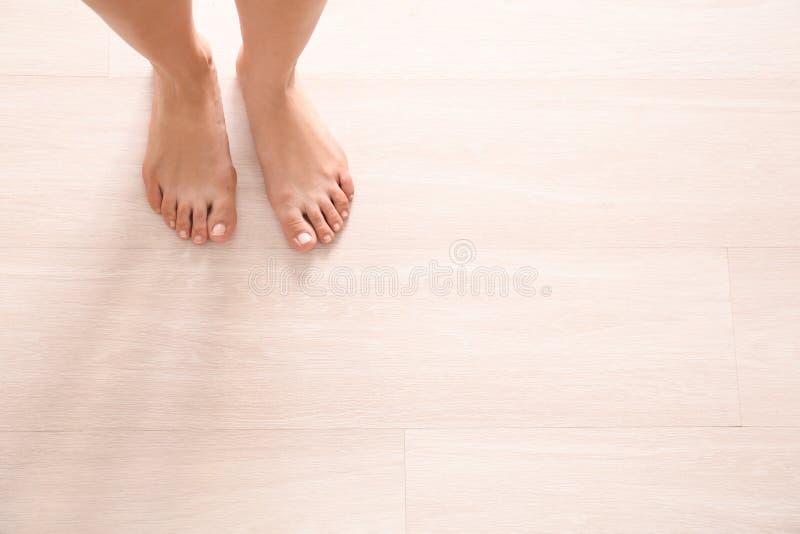 Gambe della condizione scalza della donna sul pavimento di legno immagini stock libere da diritti