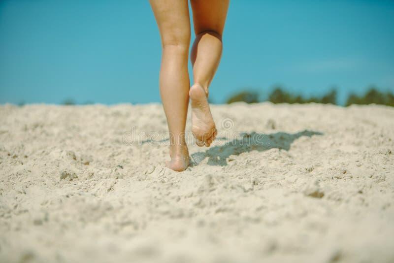 Gambe della donna che camminano entro l'ora legale della spiaggia di sabbia fotografia stock libera da diritti