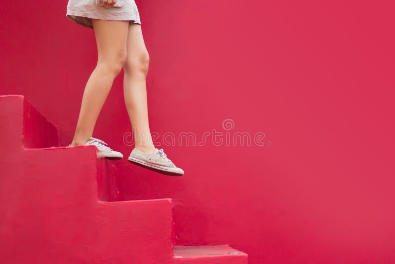 Gambe della donna che camminano giù la scala rossa con lo spazio della copia immagine stock