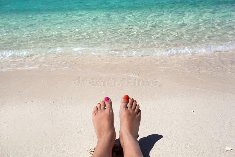 Gambe della donna che si trovano sulla spiaggia sabbiosa immagini stock