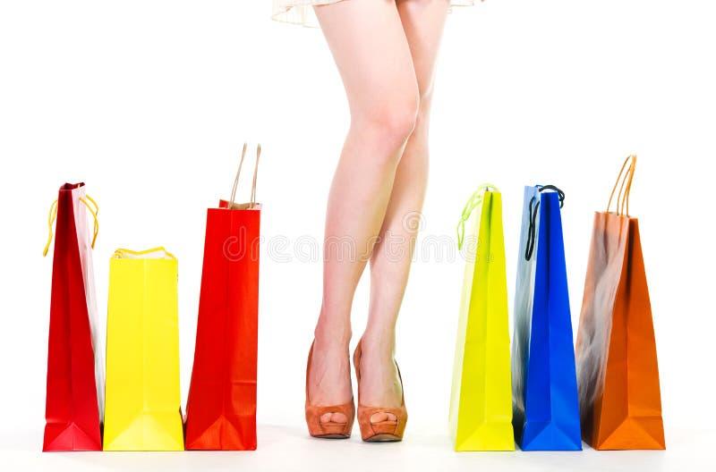 Gambe della donna con i sacchetti della spesa immagini stock libere da diritti