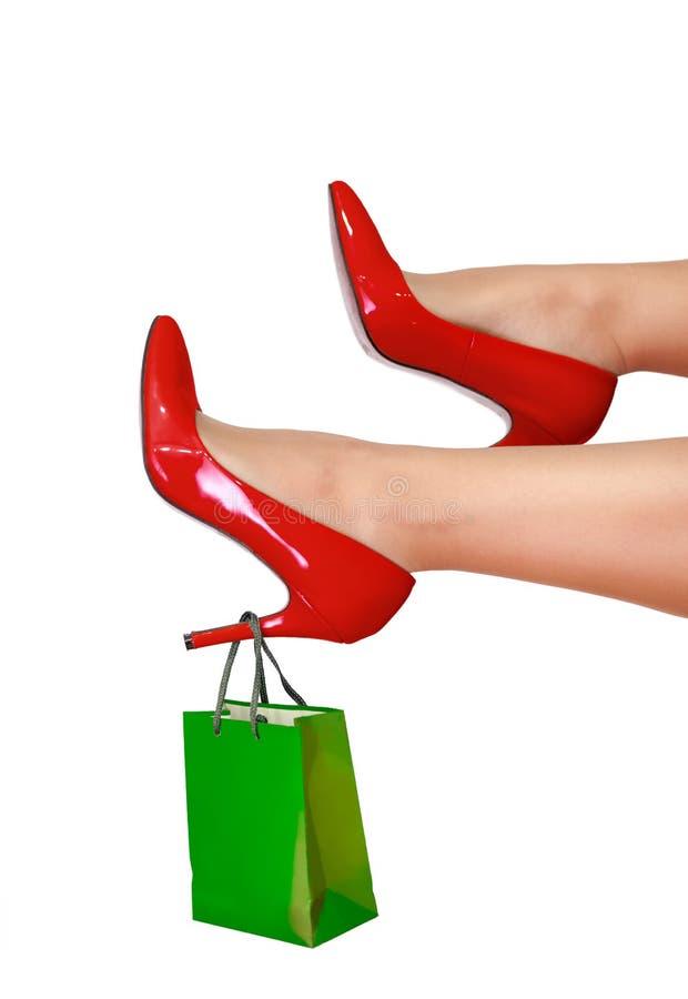 Gambe della donna con il sacchetto della spesa sul tallone fotografie stock libere da diritti