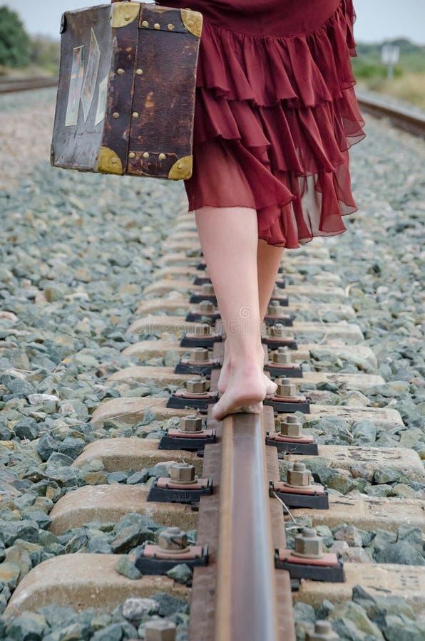 Gambe della donna con la valigia che cammina a piedi nudi sulla pista del treno immagine stock libera da diritti