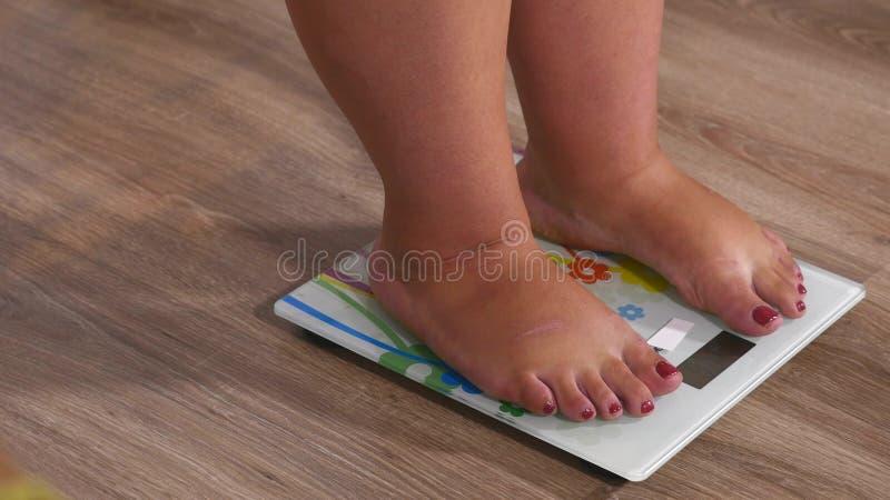 Gambe della donna del primo piano che si avvicinano a pesare strumento digitale e condizione sullo skale immagini stock libere da diritti