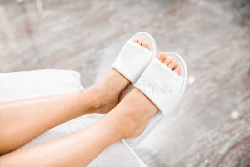 Gambe della donna in pantofole del bagno fotografia stock libera da diritti