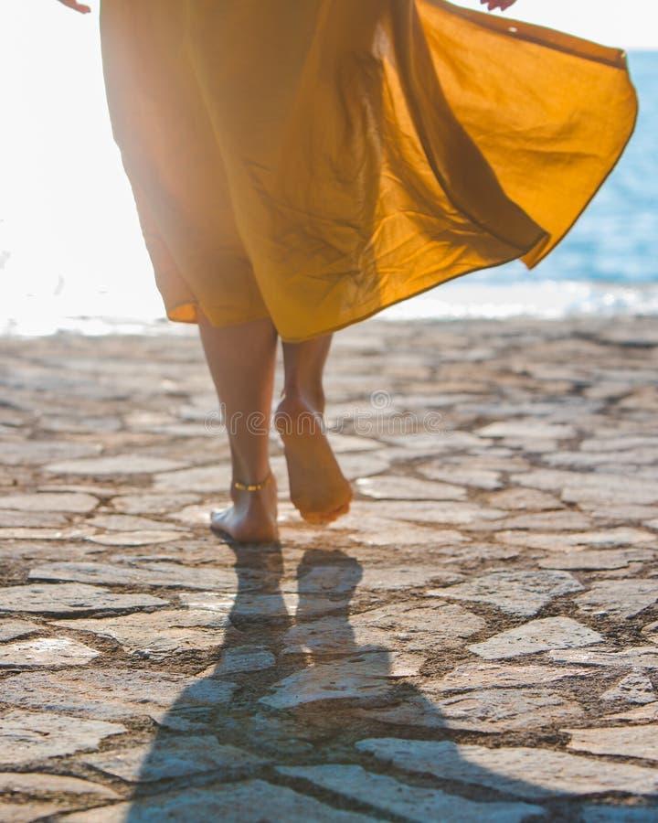 gambe della donna in prendisole gialle che camminano al mare dalla spiaggia di pietra immagini stock