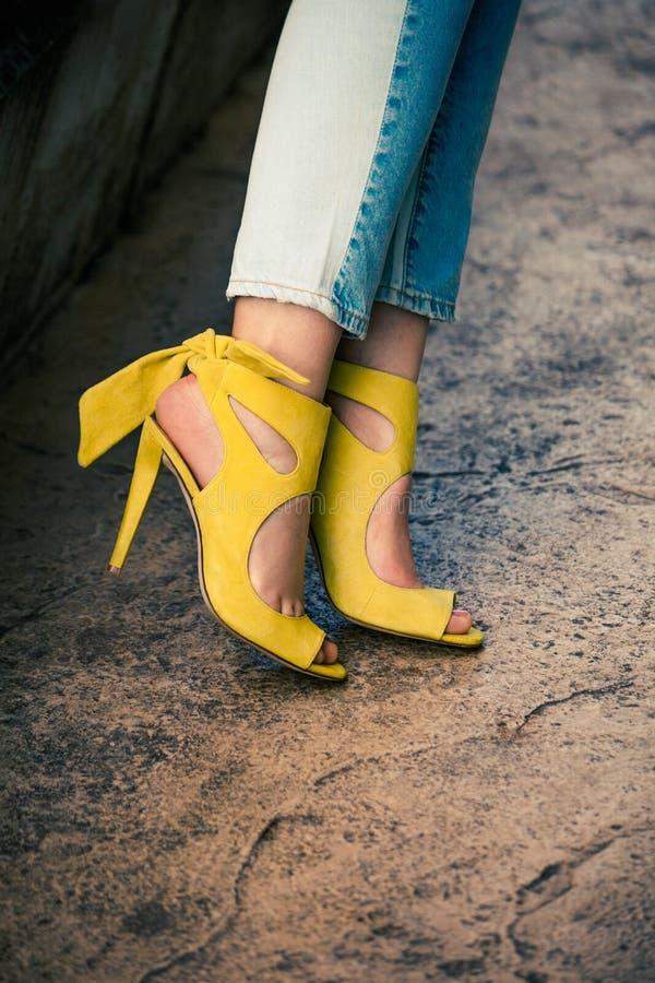 Gambe della donna in sandali gialli di cuoio del tacco alto all'aperto in città immagine stock