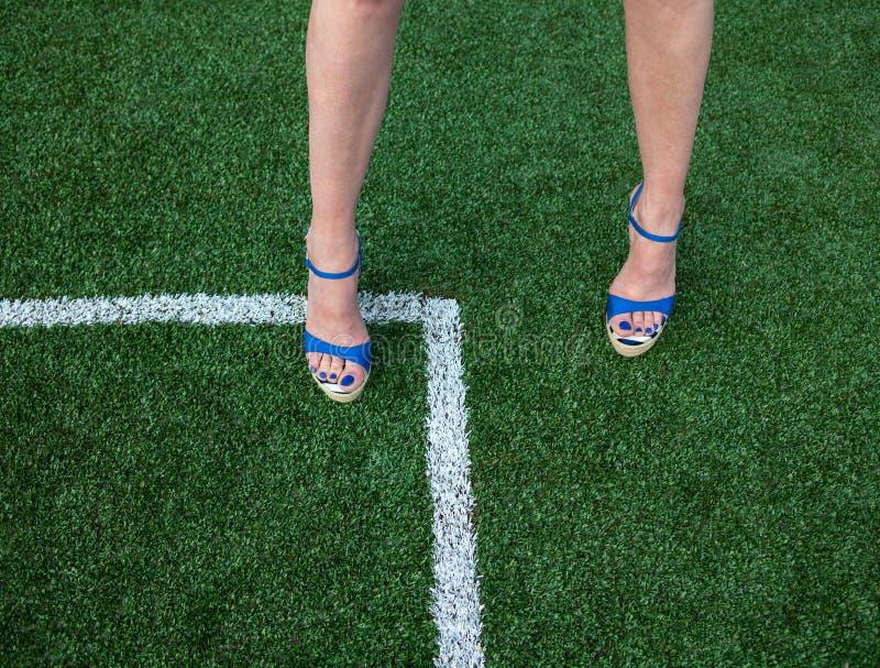 Gambe della donna sul campo di calcio immagine stock libera da diritti