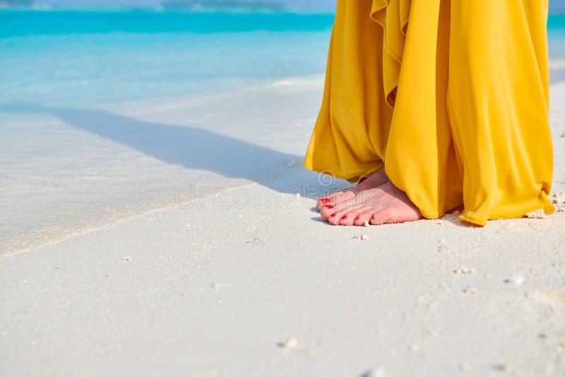 Gambe della donna in vestito giallo sulla spiaggia tropicale fotografia stock