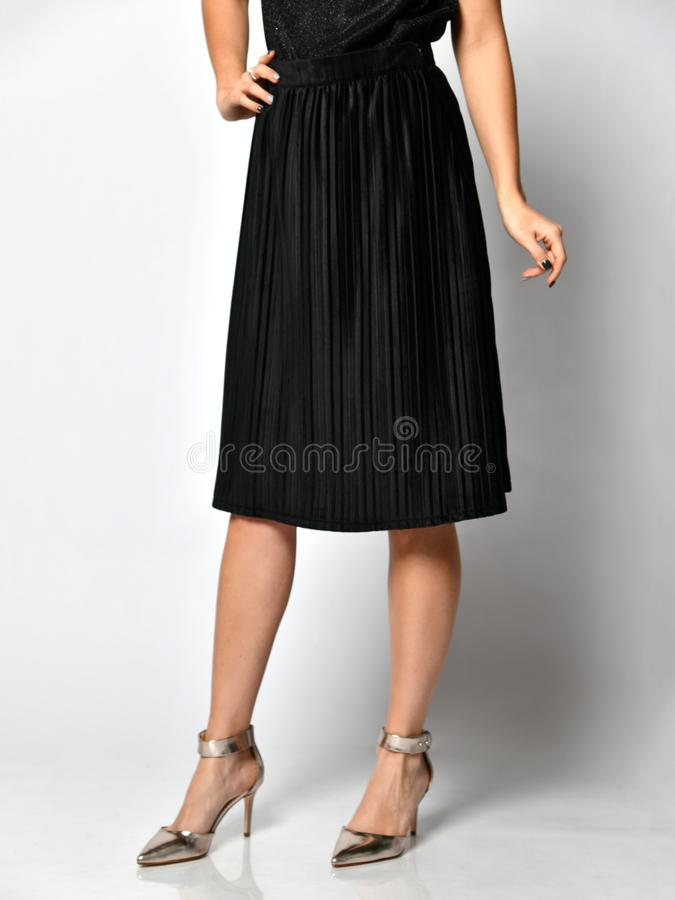 Gambe della donna in vestito nero dalla gonna in scarpe medie d'argento delle colline su grigio immagini stock libere da diritti