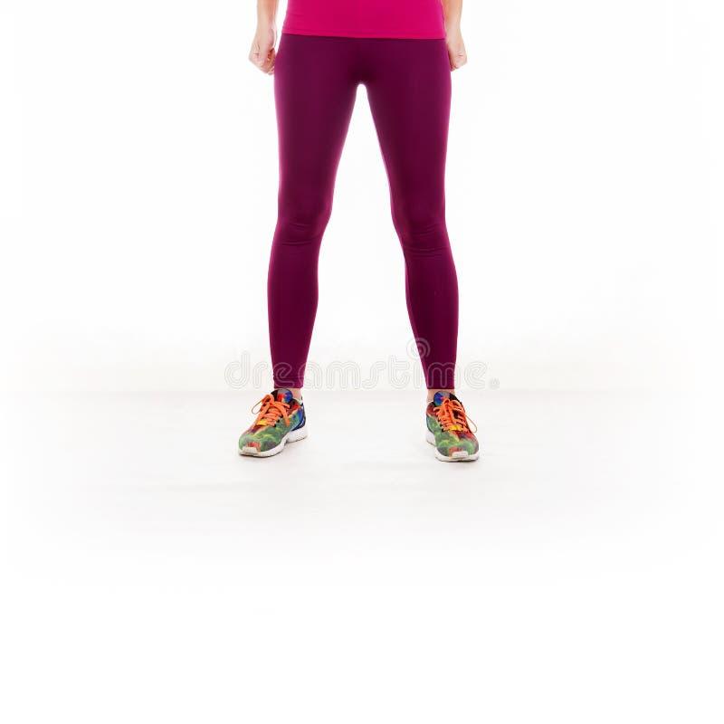 Gambe della giovane donna isolate su fondo bianco fotografia stock