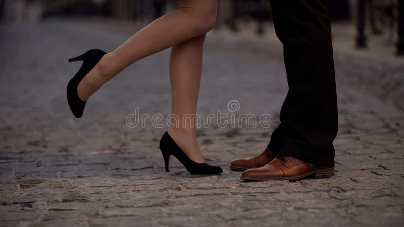 Gambe della ragazza allegra che baciano il suo ragazzo, partner dal sito Web di datazione, romanzesco fotografia stock