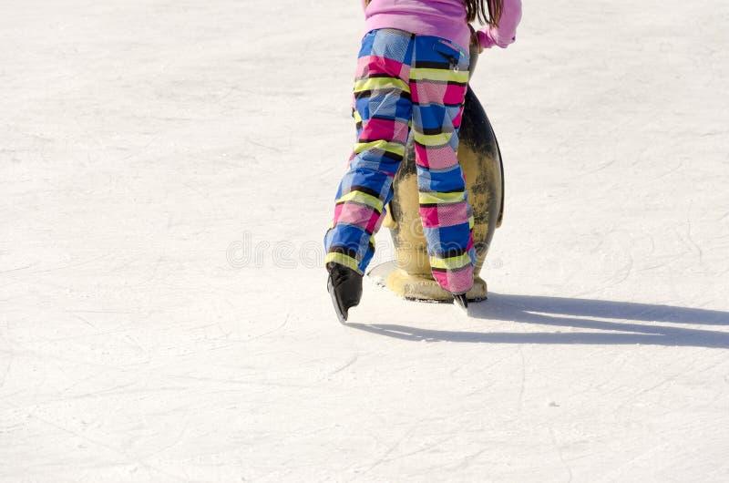 Gambe della ragazza del pattinatore su ghiaccio che imparano pattinaggio su ghiaccio sulla pista di pattinaggio sul ghiaccio immagine stock