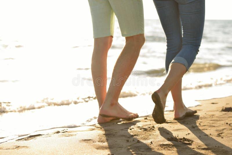 Gambe delle coppie sulla spiaggia di sabbia immagine stock