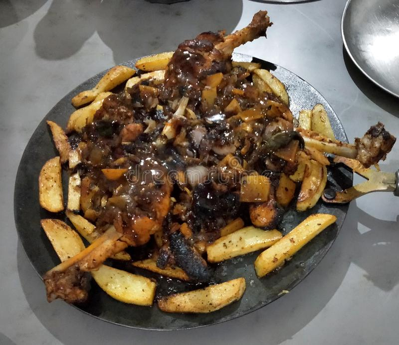 Gambe di Fried Chicken con le patate e la salsa barbecue carbonizzate fotografia stock