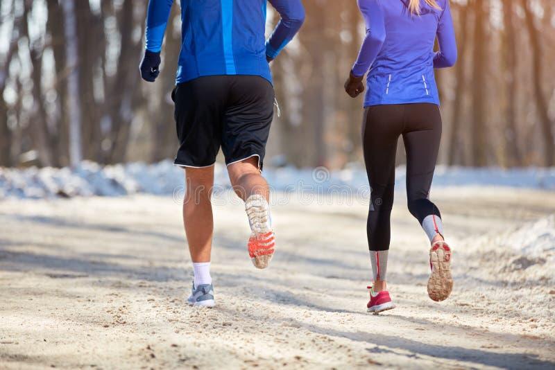 Gambe di giovane atleta mentre correndo, vista posteriore immagini stock