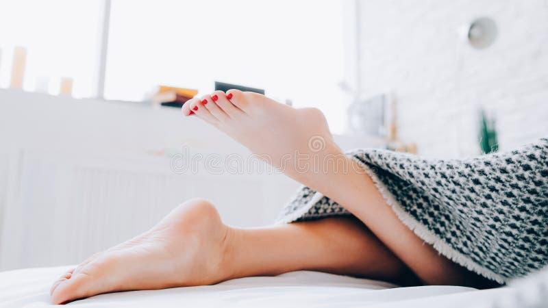 Gambe di menzogne del letto della donna scalza di igiene del piede immagini stock libere da diritti