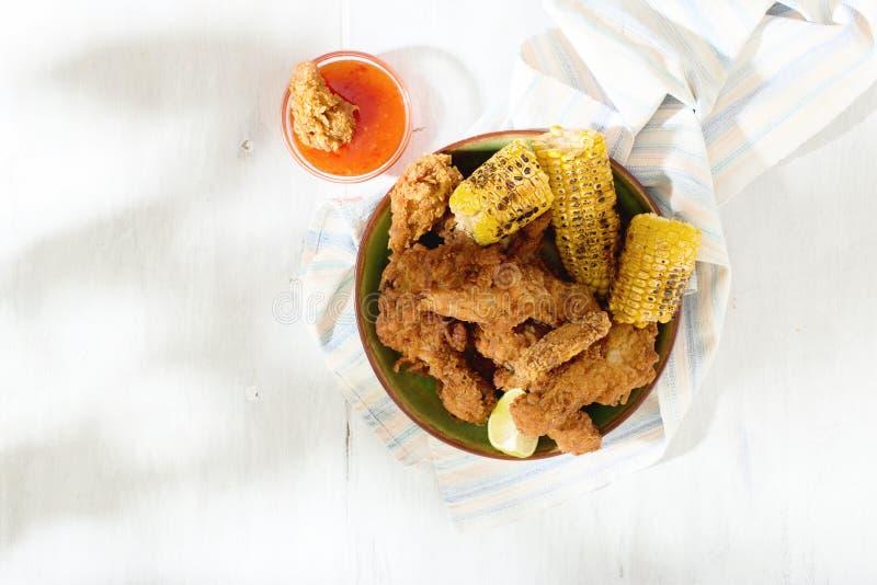 Gambe di pollo fritto con mais arrostito e salsa piccante rossa immagine stock